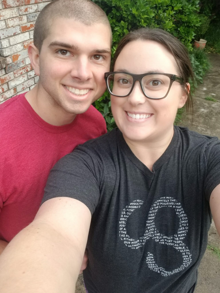 Cassie and her husband Jonathan smiling at the camera for a selfie outside their home.